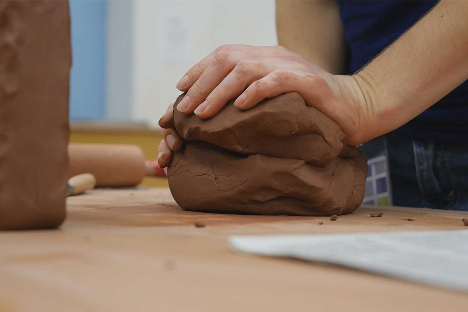 A closeup of brown clay being molded